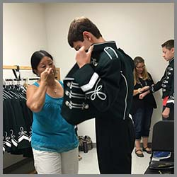 Parent helping student try on uniform
